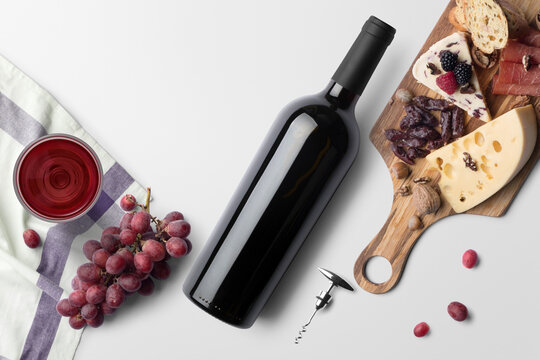 A picnic scene of red wine, cheese, nuts, meat, and fruit on a white background. A glass or wine rests on a towel with corkscrew and red grapes scattered around.