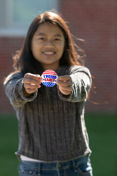 Cute Taiwanese woman Voter holding an Early Voting Sticker