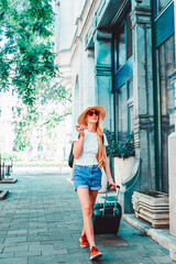 Shot of young woman walking on the street with her suitcase while on city break