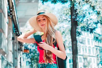 Pretty young woman wearing straw hat and backpack while standing on the street