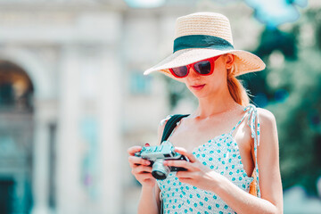 Young woman using her vintage camera while traveling alone