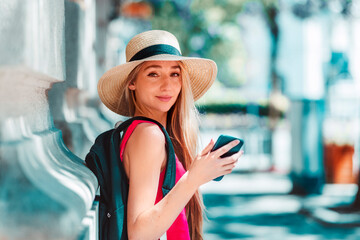 Happy young woman wearing straw hat while standing on the street and text messaging