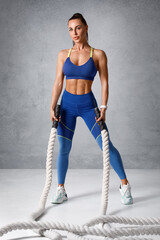 Fitness woman working out with heavy ropes. Athletic girl in sportswear