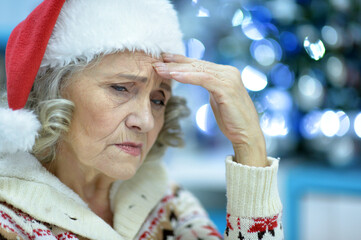 sad senior woman in Santa hat
