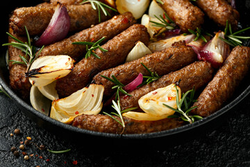 Rosemary and onion vegetarian vegan sausages oven baked in cast iron skillet frying pan