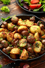Baked potato with mushrooms and herbs in iron cast pan on wooden table
