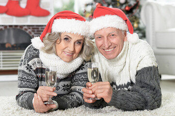 Happy senior couple in Santa hats with champagne