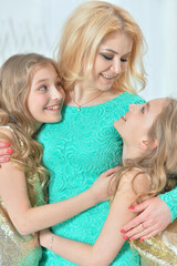 Cute smiling twin sisters hugging their mother