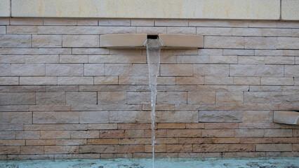Fontaine murale en pierres dorées de la place de Lozanne 69380