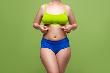 Beauty woman in multicolored underwear on green background