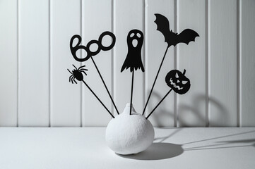 Halloween home decorations. Painted white pumpkin and black Halloween scary shadow puppets on...