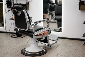 Classic vintage barber chair stands opposite mirror stylish white barber shop interior.