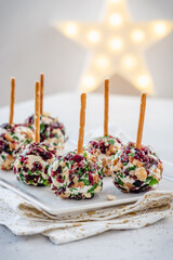 Christmas cheese ball appetizers with cranberries, pecans and herbs.