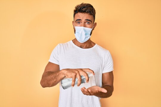 Young hispanic man wearing medical mask holding hand sanitizer gel in shock face, looking skeptical and sarcastic, surprised with open mouth