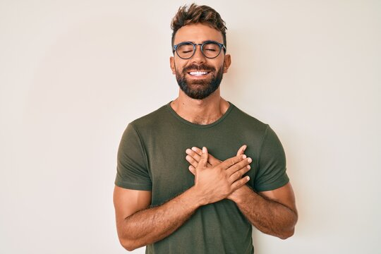 Young hispanic man wearing casual clothes and glasses smiling with hands on chest with closed eyes and grateful gesture on face. health concept.