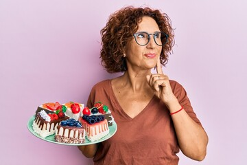 Beautiful middle age mature woman holding cake slices serious face thinking about question with hand on chin, thoughtful about confusing idea