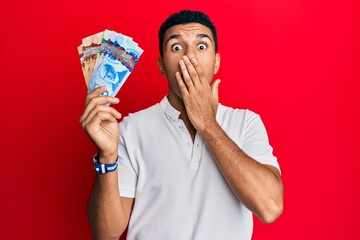 Young arab man holding canadian dollars covering mouth with hand, shocked and afraid for mistake. surprised expression
