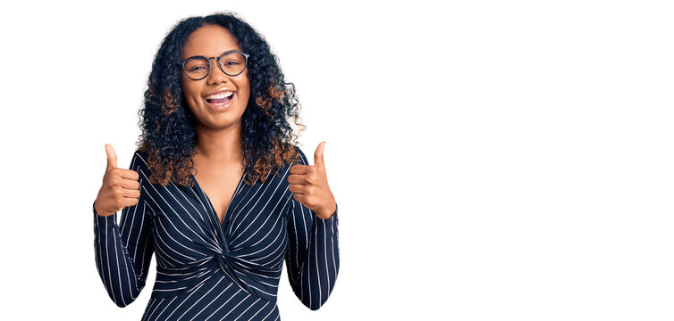 Young african american woman wearing casual clothes and glasses success sign doing positive gesture with hand, thumbs up smiling and happy. cheerful expression and winner gesture.