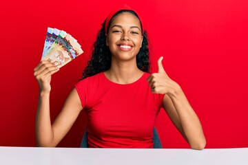 Young african american girl holding canadian dollars sitting on the table smiling happy and positive, thumb up doing excellent and approval sign