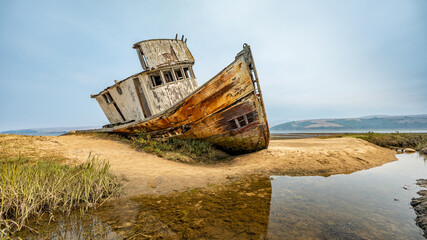 Landscape, an abandoned old ship lies aground, on the coast, California