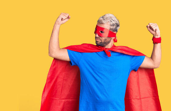 Young blond man wearing super hero custome showing arms muscles smiling proud. fitness concept.