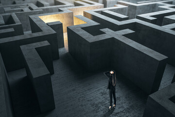Young businesswoman in suit standing in concerete gray labyrinth.