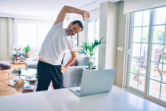 Middle age man with beard training and stretching doing exercise at home looking at sport video on computer