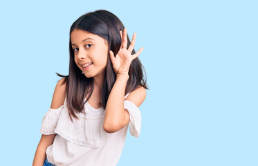 Beautiful child girl wearing casual clothes smiling with hand over ear listening an hearing to rumor or gossip. deafness concept.