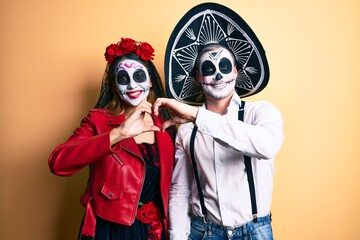 Couple wearing day of the dead costume over yellow smiling in love doing heart symbol shape with hands. romantic concept.