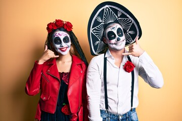 Couple wearing day of the dead costume over yellow smiling doing phone gesture with hand and fingers like talking on the telephone. communicating concepts.