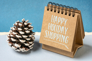 happy holiday shopping - spiral notebook sign with a decorative frosty pine cone. winter holidays shopping concept