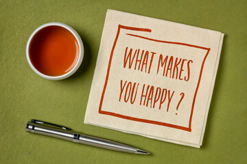 What makes you happy? A question handwritten on a napkin with a cup of tea against green handmade paper, happiness and personal development concept.