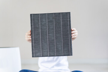 Asian woman wearing a hygiene protective face mask during changing a dirty air filter in the air purifier machine close up with copyspace. Hygienic lifestyle and prevention from illness concept.
