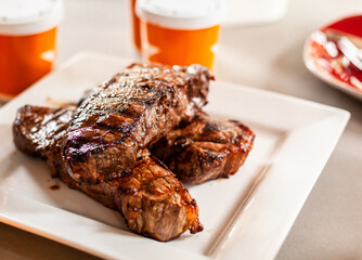 Grilled New York Strip Cut Beef - Barbeque Meat ready to eat, presented on a white Plate, with Sides Containers in Background, shallow DoF