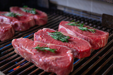 Many Fresh New York Strip Cut Beef - Barbeque Meat on a Grill, decorated with Rosemary