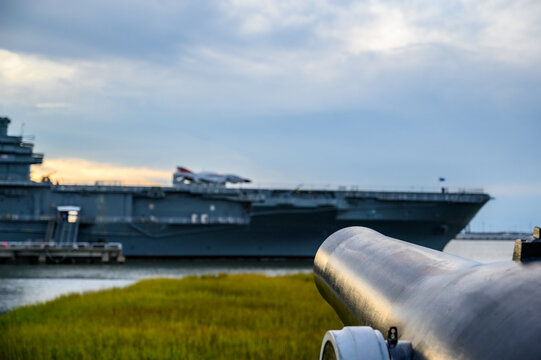 Antique cannon aimed at a modern aircraft carrier