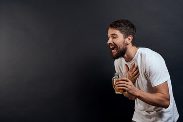 Man with a mug of beer in his hands emotions fun lifestyle white t-shirt dark isolated background