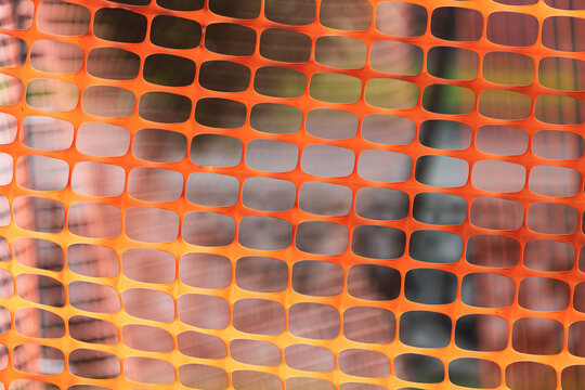 Close-up of an orange plastic mesh. Temporary fence for renovation work