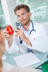 doctor holding and showing a medicine bottle