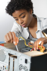 concentrated young woman fixing a desktop computer