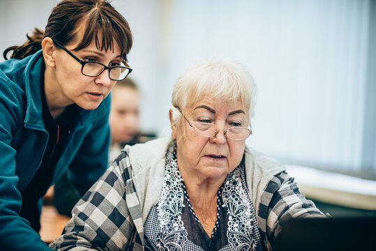 Elderly woman and teacher sitting in front of laptop in class. Training of pensioners on modern technologies