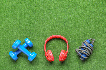 Dumbbells, jumping rope and headphones on color background