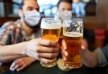 people, leisure and pandemic concept - male friends wearing face protective medical masks for protection from virus disease drinking beer and clinking glasses at bar or pub