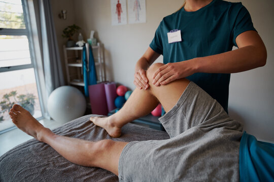 Closeup of young female physiotherapist hands giving leg exercise to patient in clinic