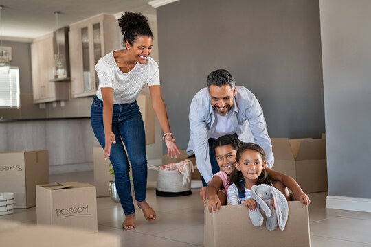 Parents playing with children while moving into new home