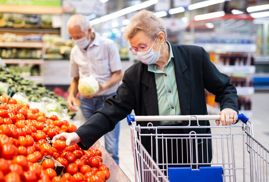 mature woman in mask and gloves with covid picks tomatoes in vegetable section of supermarket