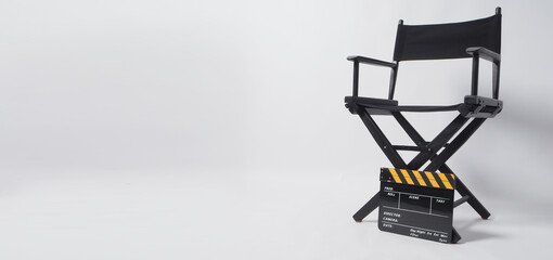 Director chair with black and yellow clapper board or movie slate on white background.it is used in...