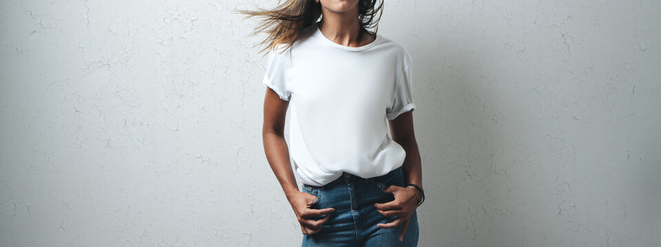 Joyful woman in white blank t-shirt, grunge wall, horizontal studio portrait. Wide screen, panoramic