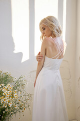 Romantic sexy woman in a long white wedding dress is standing near the window in chamomile flowers....