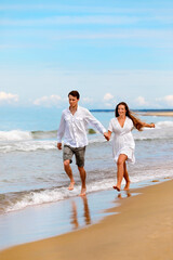 Nice couple of young people in love have fun on the sea coast